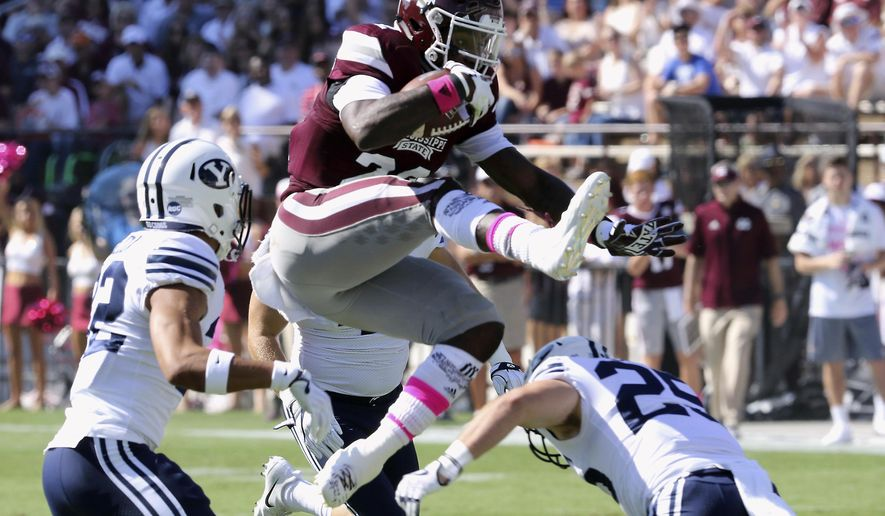 Mississippi State running back Aeris Williams (22) hurdles over BYU defensive back Tanner Jacobson (25) during the first half of an NCAA college football game in Starkville, Miss., Saturday, Oct. 14, 2017. (AP Photo/Jim Lytle)