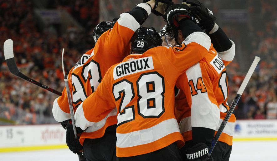 Philadelphia Flyers gather to celebrate the goal by Claude Giroux, center, during the second period of an NHL hockey game against the Washington Capitals, Saturday, Oct. 14, 2017, in Philadelphia. (AP Photo/Chris Szagola)