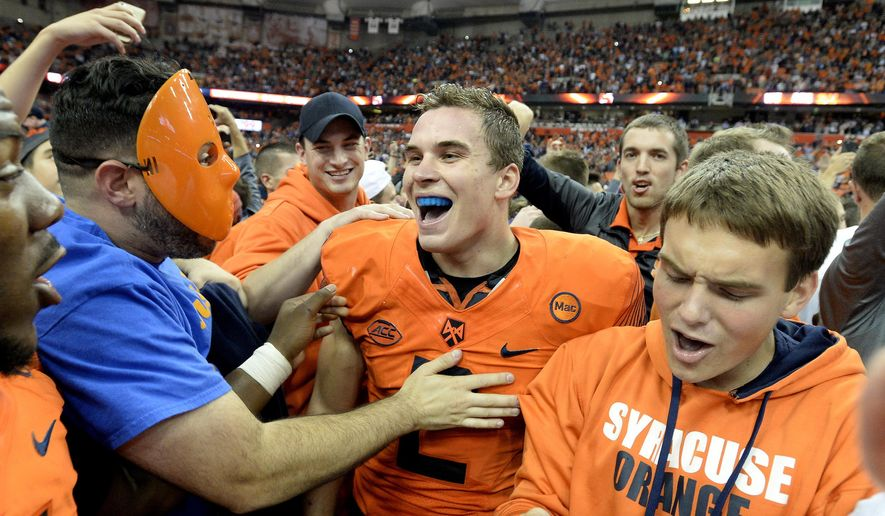 Syracuse quarterback Eric Dungey center, celebrates with fans after his win over Clemson in an NCAA college football game, Friday, Oct. 13, 2017, in Syracuse, N.Y. Syracuse upset Clemson 27-24. (AP Photo/Adrian Kraus)