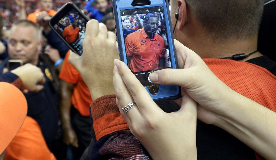 A fan who rushed the field takes a photo of Syracuse coach Dino Babers as he is being interviewed following his win over Clemson in an NCAA college football game, Friday, Oct. 13, 2017, in Syracuse, N.Y. Syracuse upset No. 2 Clemson, 27-24. (AP Photo/Adrian Kraus)