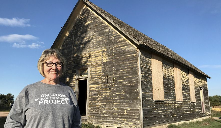 This Sept. 29, 2017 photo shows Gloria Christainsen standing in front of the long-abandoned District 70 School near Clearwater, Neb.  Christiansen, a retired grade school teacher at Clearwater and media instructor with the local educational service unit, has been on a mission for the past year to move the District 70 School, known as the Midland School, to a county complex of historic structures in Neligh. (Paul Hammel/Omaha World-Herald via AP)