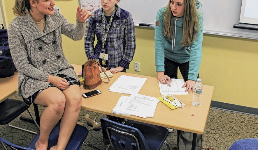 In this Monday, Oct. 2, 2017, photo, Eagle River High School students, from left, Jenni Hunting, Sara George and Alina Cook discuss story ideas during a meeting of the ERHS newspaper club in Eagle River, Alaska. The new school newspaper plans on publishing its first print edition this fall. (Kirsten Swann/Alaska Journal of Commerce via AP)