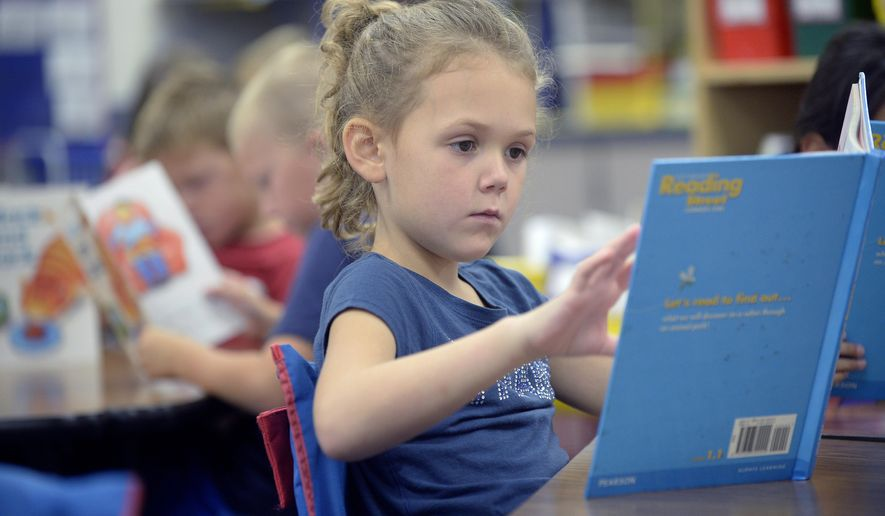 In an Oct. 6, 2017 photo, Norris first-grader Ainsley Pegans turns a page as she reads in Vicki Miles' class in Hickman, Neb. For younger students, the new English language arts assessments test both reading and writing skills and follow more-rigorous standards than previous tests. (Eric Gregory/The Journal-Star via AP)
