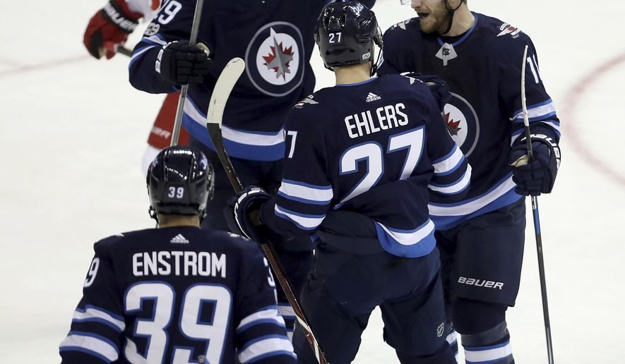 Winnipeg Jets' Toby Enstrom (39), Patrik Laine (29), Nikolaj Ehlers (27) and Bryan Little (18) celebrate after Little scored during the first period of an NHL hockey game against the Carolina Hurricanes, Saturday, Oct. 14, 2017 in Winnipeg, Manitoba. (Trevor Hagan/The Canadian Press via AP)