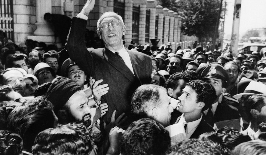 FILE- In this Sept. 27, 1951 file photo, Prime Minister Mohammed Mosaddegh rides on the shoulders of cheering crowds in Tehran's Majlis Square, outside the parliament building, after reiterating his oil nationalization views to his supporters. (AP Photo, File)