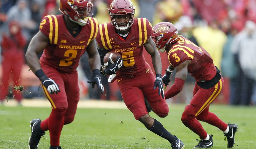 Iowa State defensive back Kamari Cotton-Moya (5) returns an interception between teammates Willie Harvey, left, and Reggie Wilkerson, right, during the first half of an NCAA college football game against Kansas, Saturday, Oct. 14, 2017, in Ames, Iowa. (AP Photo/Charlie Neibergall)