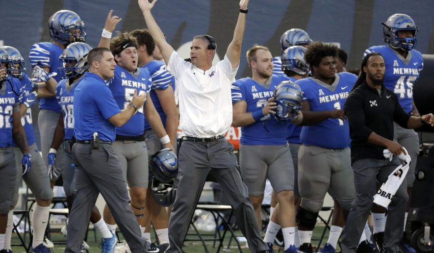 Memphis head coach Mike Norvell celebrates after defensive back Austin Hall intercepted a pass to seal a 30-27 upset win over Navy in the final minutes of the fourth quarter in an NCAA college football game Saturday, Oct. 14, 2017, in Memphis, Tenn. (AP Photo/Mark Humphrey)
