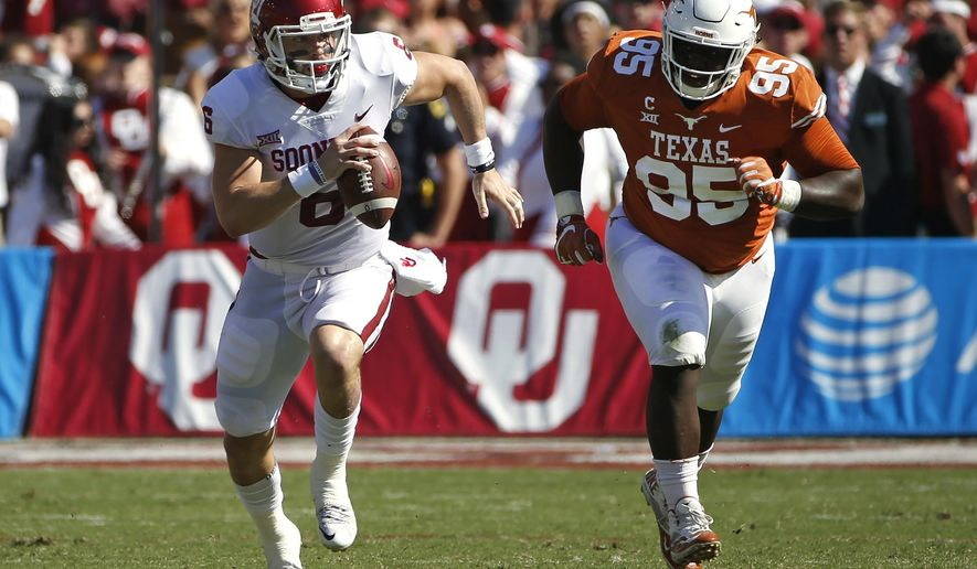 Oklahoma quarterback Baker Mayfield (6) scrambles for a first down as Texas defensive lineman Poona Ford (95) pursues during the first half of an NCAA college football game Saturday, Oct. 14, 2017, in Dallas, Texas. (AP Photo/Ron Jenkins)