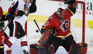 Ottawa Senators' Ryan Dzingel, left, watches as Calgary Flames goalie Mike Smith lets in a goal during the third period of an NHL hockey game Friday, Oct. 13, 2017, in Calgary, Alberta. (Jeff McIntosh/The Canadian Press via AP)