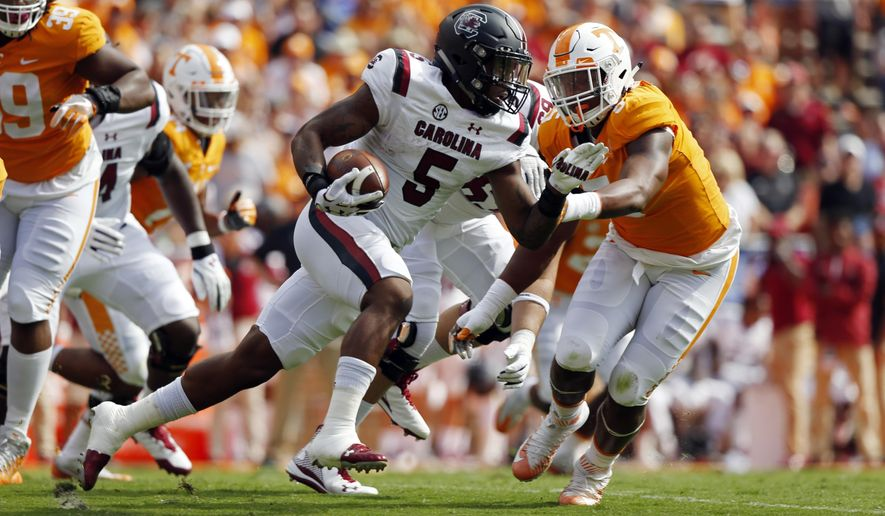 South Carolina running back Rico Dowdle (5) runs for yardage as he's chased by Tennessee defensive lineman Kyle Phillips (5) in the first half of an NCAA college football game Saturday, Oct. 14, 2017, in Knoxville, Tenn. (AP Photo/Wade Payne)