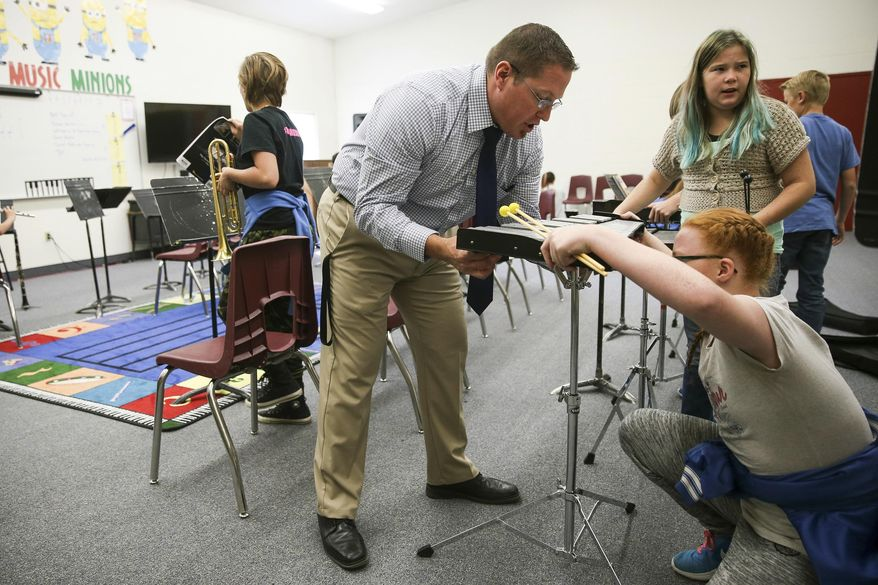 In this Thursday, Sept. 28, 2017 photo, Kodey Hughes, superintendent of the Tintic School District, teaches a music class at Eureka Elementary in Eureka, Utah. (Spenser Heaps/The Deseret News via AP)