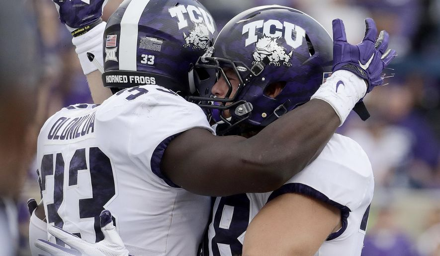 TCU running back Sewo Olonilua (33) celebrates with tight end Daythan Davis (38) after scoring a touchdown during the second half of an NCAA college football game against Kansas State, Saturday, Oct. 14, 2017, in Manhattan, Kan. (AP Photo/Charlie Riedel)