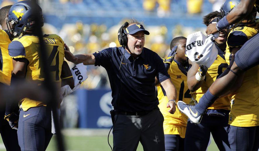 West Virginia head coach Dana Holgorsen celebrates a touchdown with his team during the second half of an NCAA college football game against Texas Tech, Saturday, Oct. 14, 2017, in Morgantown, W.Va. (AP Photo/Raymond Thompson)