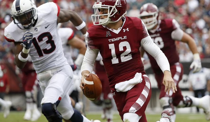 Temple's quarterback Logan Marchi, right, keeps the ball as Connecticut's Vontae Diggs, gives chase in the first half of an NCAA college football game in Philadelphia, Pa., Saturday, Oct. 14, 2017. (David Maialetti/The Philadelphia Inquirer via AP)