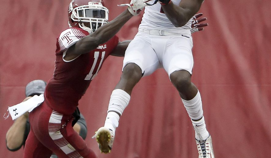 Connecticut's Tre Bell, right, catches a pass in front of Temple's Linwood Crump, left, in the end zone during the second quarter of an NCAA college football game in Philadelphia, Pa., Saturday, Oct. 14, 2017. (David Maialetti/The Philadelphia Inquirer via AP)