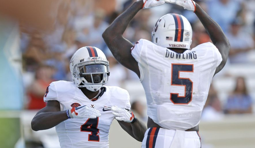 Virginia's Olamide Zaccheaus (4) and Doni Dowling (5) celebrate Zaccheaus' touchdown against North Carolina during the second half an NCAA college football game in Chapel Hill, N.C., Saturday, Oct. 14, 2017. (AP Photo/Gerry Broome)