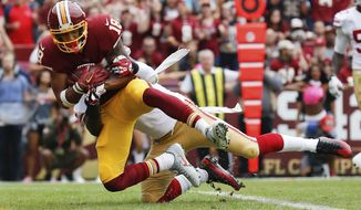 Washington Redskins wide receiver Josh Doctson (18) pulls in a touchdown pass as San Francisco 49ers free safety Jaquiski Tartt (29) pulls him to the turf during the first half of an NFL football game in Landover, Md., Sunday, Oct. 15, 2017. (AP Photo/Alex Brandon)