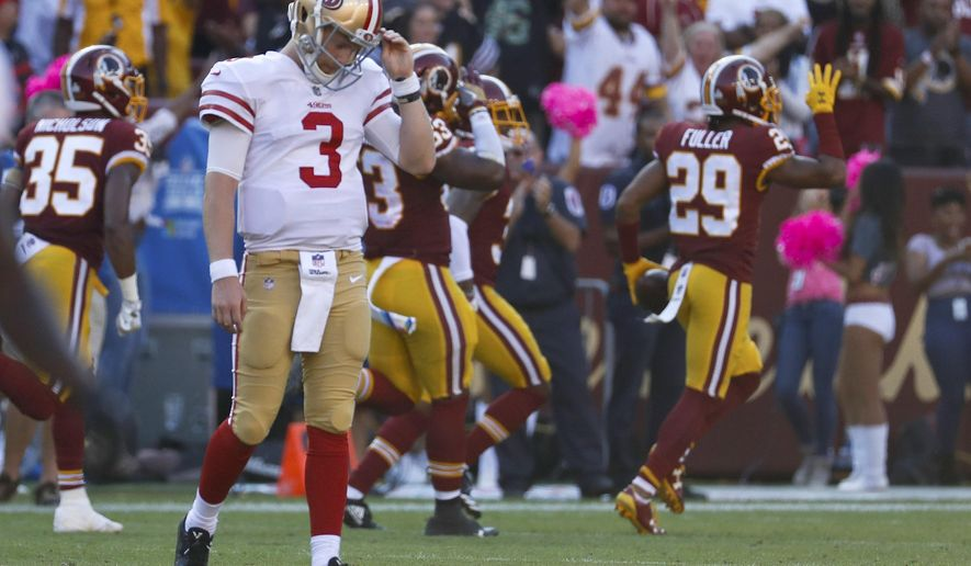 San Francisco 49ers quarterback C.J. Beathard (3) walks off the field as Washington Redskins cornerback Kendall Fuller (29) celebrates his interception that ended the game during the second half of an NFL football game in Landover, Md., Sunday, Oct. 15, 2017. The Redskins defeated the 49er 26-24. (AP Photo/Alex Brandon)