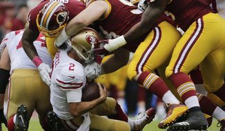 San Francisco 49ers quarterback Brian Hoyer (2) is sacked by Washington Redskins outside linebacker Preston Smith (94) and defensive tackle Matthew Ioannidis (98) during the first half of an NFL football game in Landover, Md., Sunday, Oct. 15, 2017. (AP Photo/Mark Tenally)