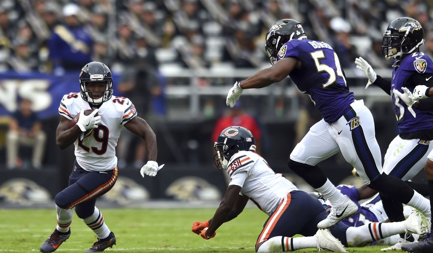Chicago Bears running back Tarik Cohen, left, rushes the ball past Baltimore Ravens defenders in the first half of an NFL football game, Sunday, Oct. 15, 2017, in Baltimore. (AP Photo/Gail Burton)