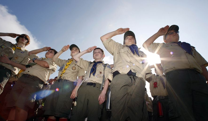 """In this Saturday morning, May 21, 2011 file photo, Boy Scouts salute during a """"camporee"""" in Sea Girt, N.J. The Wednesday, Oct. 11, 2017 Boy Scouts of America announcement to admit girls throughout its ranks will transform what has been a mostly cordial relationship between the two iconic youth groups since the Girl Scouts of the USA was founded in 1912, two years after the Boy Scouts. (AP Photo/Mel Evans) FILE"""