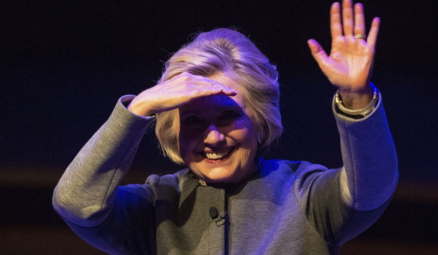 "Hillary Rodham Clinton shields her eyes from the lights and waves to the audience, after speaking during the London Literature Festival event at the Royal Festival Hall in London, Sunday Oct. 15, 2017.  Clinton is in London talking about her new book ""What Happened"", charting the electoral defeat of the U.S. Democratic presidential candidate. (Dominic Lipinski/PA via AP)"