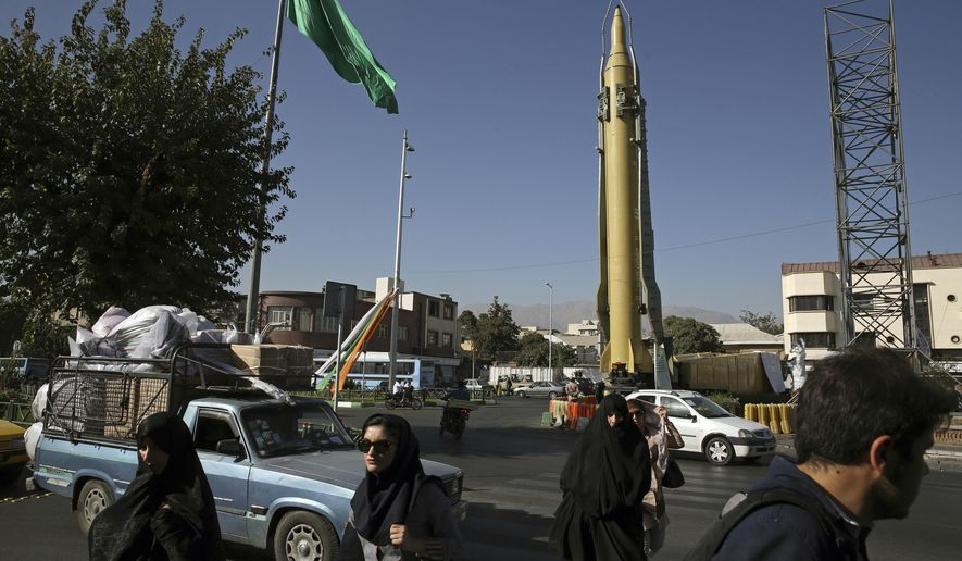 FILE - In this  Sept. 25, 2016 file photo, Iranians walk past a Ghadr-F missile displayed at a Revolutionary Guard hardware exhibition, marking 36th anniversary of the outset of Iran-Iraq war, at Baharestan Sq. in downtown Tehran, Iran. U.S. President Donald Trump angered Iran with his speech on refusing to re-certify the nuclear deal, but Tehran is unlikely to walk away from the agreement in retaliation. (AP Photo/Vahid Salemi, File)