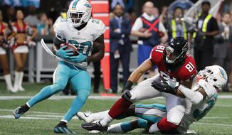 Miami Dolphins free safety Reshad Jones (20) picks up the ball against Atlanta Falcons tight end Austin Hooper (81) during the second half of an NFL football game, Sunday, Oct. 15, 2017, in Atlanta. The Miami Dolphins won 20-17. (AP Photo/David Goldman)