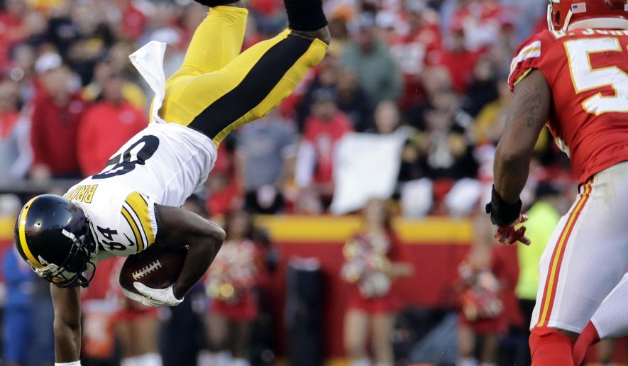 Kansas City Chiefs linebacker Derrick Johnson, right, watches as Pittsburgh Steelers wide receiver Antonio Brown (84) is flipped by a tackle by Chiefs linebacker Kevin Pierre-Louis during the second half of an NFL football game in Kansas City, Mo., Sunday, Oct. 15, 2017. (AP Photo/Charlie Riedel)