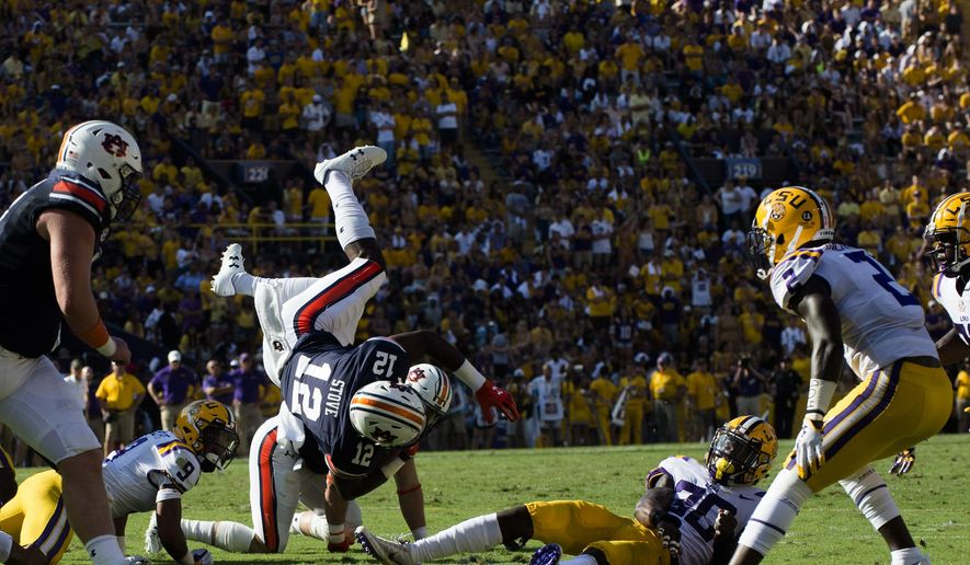 Auburn wide receiver Eli Stove (12) is tackled by LSU defensive back Eric Monroe (30) during an NCAA college football game in Baton Rouge, La., Saturday, Oct. 14, 2017.  (Albert Cesare/The Montgomery Advertiser via AP)