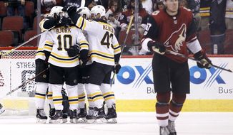 Boston Bruins' Anders Bjork (10) celebrates with Danton Heinen (43) and teammates after scoring a third-period goal as Arizona Coyotes' Lawson Crouse skates off the ice during an NHL hockey game, Saturday, Oct. 14, 2017, in Glendale, Ariz. The Bruins defeated the Coyotes 6-2. (AP Photo/Ralph Freso)