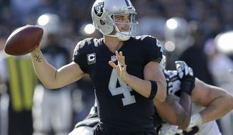 Oakland Raiders quarterback Derek Carr (4) passes against the Los Angeles Chargers during the second half of an NFL football game in Oakland, Calif., Sunday, Oct. 15, 2017. (AP Photo/Ben Margot)