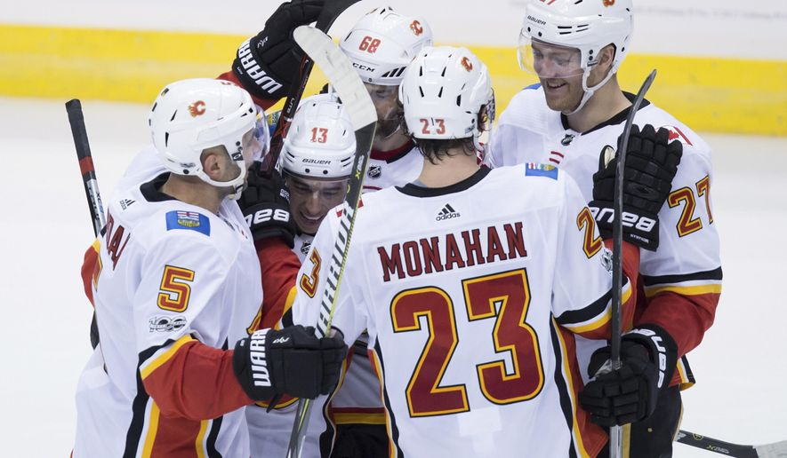 Calgary Flames' Mark Giordano, Johnny Gaudreau, Jaromir Jagr, of the Czech Republic, Sean Monahan and Dougie Hamilton, from left, celebrate Monahan's goal during the second period of an NHL hockey game against the Vancouver Canucks in Vancouver, British Columbia, Saturday, Oct. 14, 2017. (Darryl Dyck/The Canadian Press via AP)