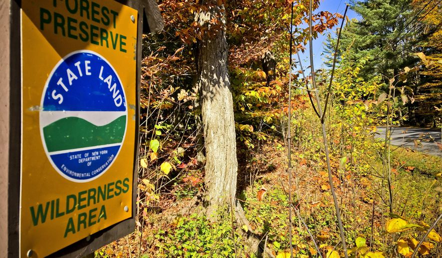 This Oct. 12, 2017 photo shows a sign marking state Forest Preserve land near a road where local officials want to put a bike lane, in Piseco Lake, N.Y. The project, which stalled because of a state constitution violation of Adirondack Forest Preserve land, could get the green light when it goes before New York voters in November. (AP Photo/Mary Esch)