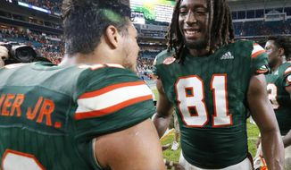 Miami wide receiver Darrell Langham (81) and quarterback Malik Rosier (12) congratulate each other after Miami defeated Georgia Tech 25-24, during an NCAA College football game, Saturday, Oct. 14, 2017 in Miami Gardens, Fla. Langham made a 28-yard catch on a tipped fourth-down ball keeping desperate Miami's drive alive and setting up Michael Badgley's 24-yard field goal with 4 seconds left. (AP Photo/Wilfredo Lee)