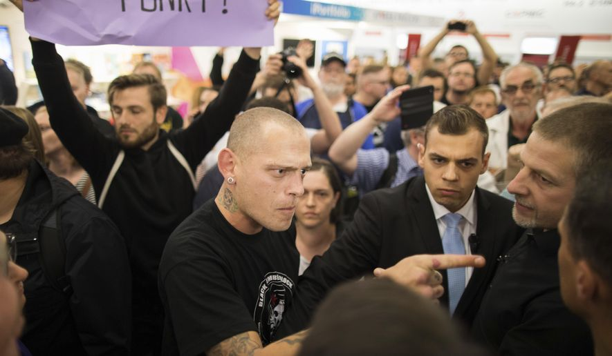 In this Oct. 14, 2017 photo protesters scuffle with stewards during a reading and discussion with Bjoern Hoecke, the head of the nationalist AfD's faction in the Thuringia state legislature at the the Frankfurt Book Fair in Frankfurt am Main, Germany. (Frank Rumpenhorst/dpa via AP)