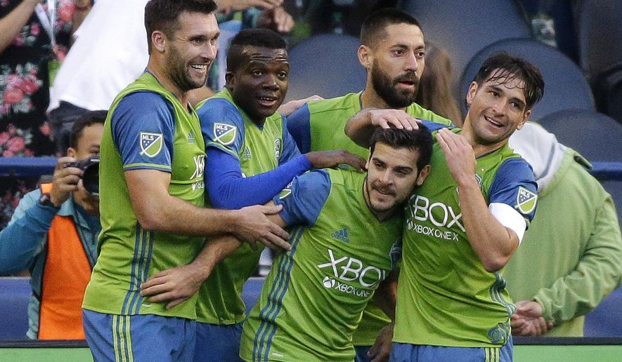 Seattle Sounders' Victor Rodriguez, second from lower right, is greeted by teammates after he scored a goal against FC Dallas in the first half of an MLS soccer match, Sunday, Oct. 15, 2017, in Seattle. (AP Photo/Ted S. Warren)