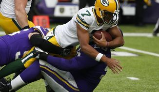 Green Bay Packers quarterback Brett Hundley (7) is tackled by Minnesota Vikings defensive end Brian Robison (96) and Linval Joseph (98) in the second half of an NFL football game in Minneapolis, Sunday, Oct. 15, 2017. (AP Photo/Bruce Kluckhohn)