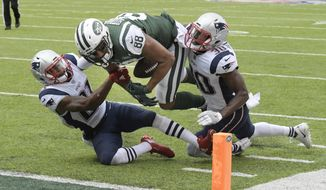 New York Jets tight end Austin Seferian-Jenkins (88) is tackled by New England Patriots' Malcolm Butler (21) and Duron Harmon (30) during the second half of an NFL football game, Sunday, Oct. 15, 2017, in East Rutherford, N.J. After further review the play was ruled a fumble into the end zone. (AP Photo/Bill Kostroun)