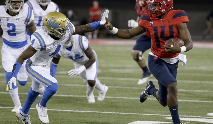 Arizona quarterback Khalil Tate (14) stiff arms UCLA defensive back Jaleel Wadood (4) and scores a touchdown in the first half during an NCAA college football game, Saturday, Oct. 14, 2017, in Tucson, Ariz. (AP Photo/Rick Scuteri)
