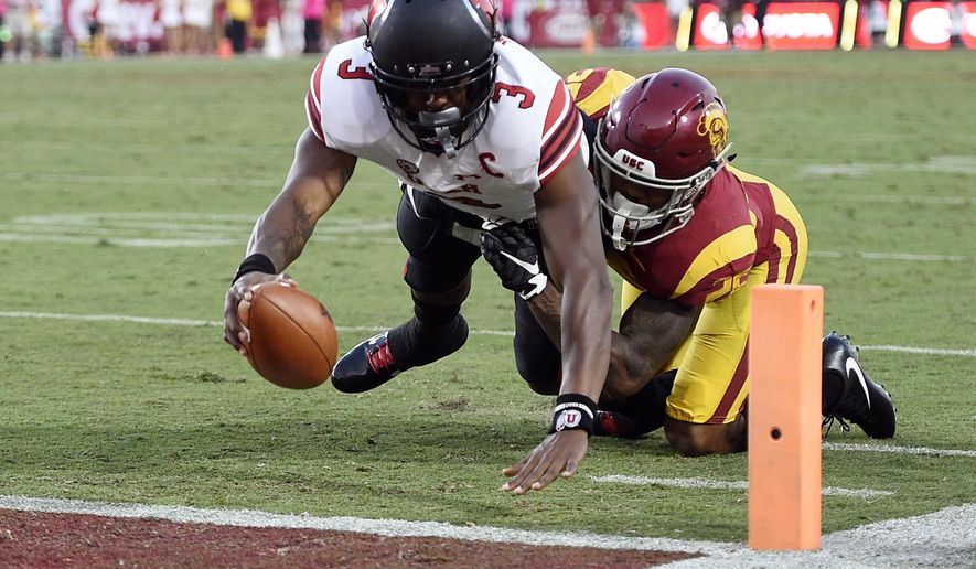 Utah quarterback Troy Williams, left, scores a touchdown while Southern California cornerback Jack Jones attempts a tackle during the first half of an NCAA college football game in Los Angeles, Saturday, Oct. 14, 2017. (AP Photo/Kelvin Kuo)