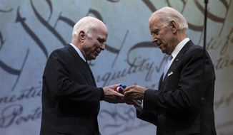 Sen. John McCain, R-Ariz., receives the Liberty Medal from Chair of the National Constitution Center's Board of Trustees, former Vice President Joe Biden, in Philadelphia, Monday, Oct. 16, 2017. The honor is given annually to an individual who displays courage and conviction while striving to secure liberty for people worldwide. (AP Photo/Matt Rourke)