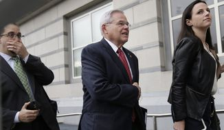 """U.S. Sen. Robert Menendez, center, arrives to court in Newark, N.J., Monday, Oct. 16, 2017. The judge in Menendez's corruption trial could rule on Monday to dismiss the bulk of the indictment against the New Jersey Democrat, a decision that prosecutors say could """"broadly legalize pay-to-play politics."""" (AP Photo/Seth Wenig)"""