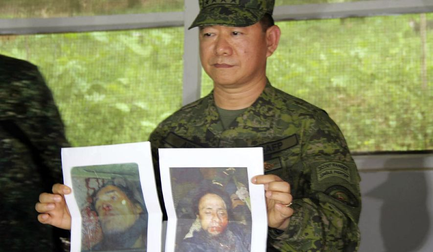 In this photo released by the 4th Civil Relations Group, Civil Relations Service Armed Forces of the Philippines, Philippine military chief Gen. Eduardo Ano holds pictures of dead militant leaders during a press conference at a military camp in Marawi, southern Philippines on Monday, Oct. 16, 2017. The last two surviving leaders of a deadly siege in the southern Philippines, including a top Asian terror suspect, were killed Monday in a push by thousands of troops to retake the last pocket of Marawi city still held by pro-Islamic State militants, top security officials said. Officials said that Isnilon Hapilon, who is listed among the FBI's most-wanted terror suspects, and Omarkhayam Maute were killed in a gunbattle and their bodies were found Monday in Marawi. (4th Civil Relations Group, Civil Relations Service Armed Forces of the Philippines via AP)