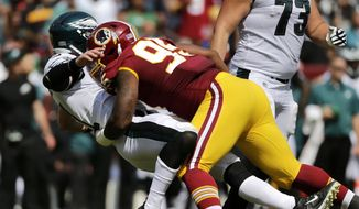 This Sept. 10, 2017, file photo shows Washington Redskins defensive end Jonathan Allen, right, tackling Philadelphia Eagles quarterback Carson Wentz as Wentz throws a pass in the first half of an NFL football game in Landover, Md. Allen, a rookie, has a Lisfranc sprain in his foot and will miss some time, according to coach Jay Gruden.(AP Photo/Mark Tenally, File)