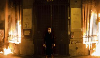 Russian artist Petr Pavlensky poses in front of a Banque de France building after setting fire to the window gates as part of a performance in Paris, Monday, Oct. 16, 2017. Pavlensky, known for macabre, politically charged actions, was being detained by police. (AP Photo/Capucine Henry)