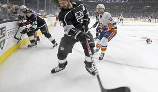 Los Angeles Kings defenseman Drew Doughty (8) loses his helmet but keeps on playing, clearing the puck against the New York Islanders in the third period of an NHL hockey game in Los Angeles, Sunday, Oct. 15, 2017. The Kings won, 3-2. (AP Photo/Reed Saxon)