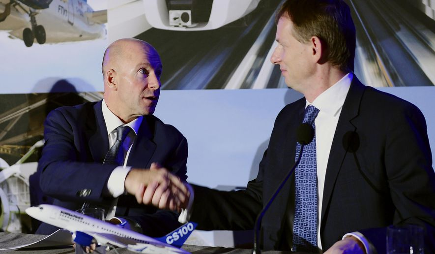 Bombardier president and CEO Alain Bellemare, left, and president Canada and chief operating officer of North America for Airbus Helicopters Romain Trapp shake hands during a press conference in Montreal on Monday, Oct. 16, 2017. Canadian plane maker Bombardier has a sold a majority stake in its C Series passenger jet business to European aerospace giant Airbus. (Paul Chiasson/The Canadian Press via AP)