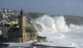 Waves break around the church in the harbour at Porthleven, Cornwall southwestern England, as the remnants of  Hurricane Ophelia begins to hit parts of Britain and Ireland. Ireland's meteorological service is predicting wind gusts of 120 kph to 150 kph (75 mph to 93 mph), sparking fears of travel chaos. Some flights have been cancelled, and aviation officials are warning travelers to check the latest information before going to the airport Monday.  (Ben Birchall/PA via AP)