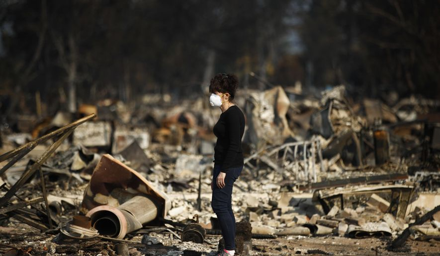 """Karen Curzon stands in what remains of her home, which was destroyed by a wildfire in the Coffey Park neighborhood, Sunday, Oct. 15, 2017, in Santa Rosa, Calif. """"We are going to rebound, rebuild and get this community back,"""" said Curzon. (AP Photo/Jae C. Hong)"""